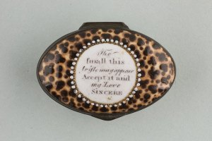Oval patch box imitating a cowrie shell with white reserve edged with white raised 'pearls' and bearing a verse.